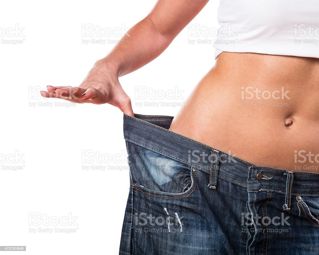 Person showing loose pants on hips as part of weight loss stock photo