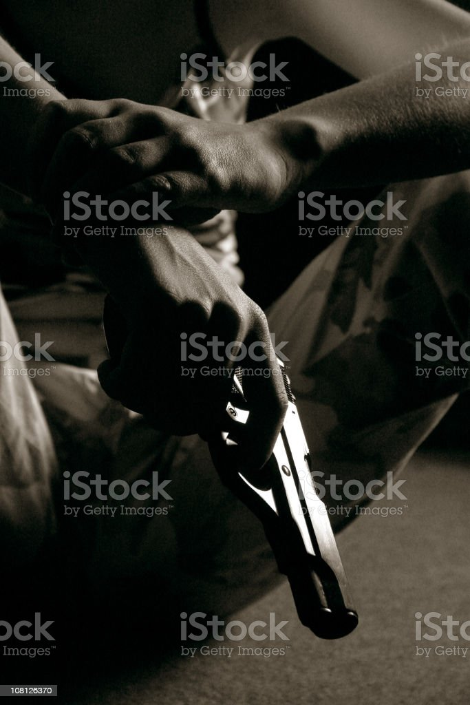 Person Sitting Down and Holding Gun, Toned stock photo