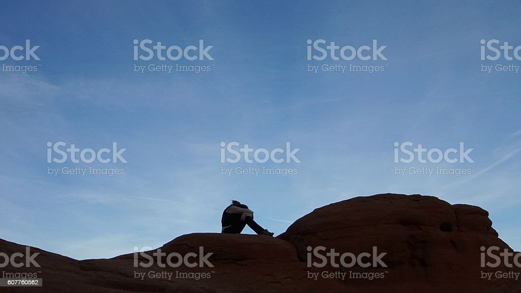 Jumping Mid-air Person Silhouette Inside Broken Arch Round Rock Formation stock photo