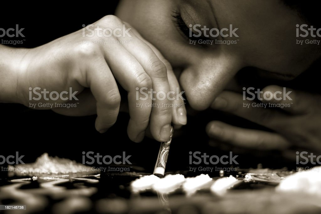 Person snorting cocaine due to addiction royalty-free stock photo