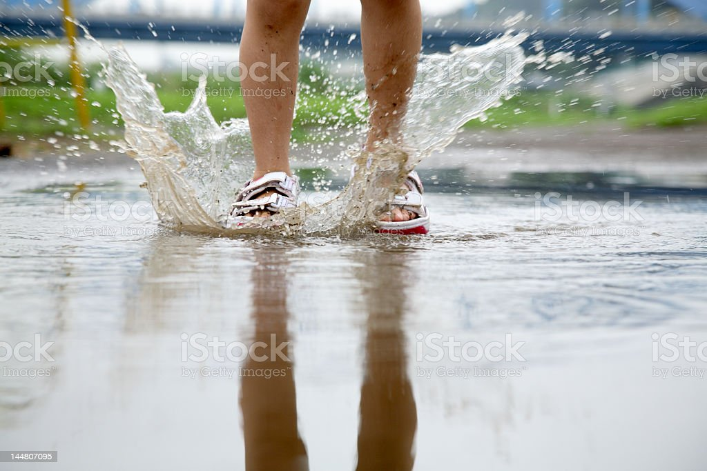 Person splashing in puddle with shoes royalty-free stock photo