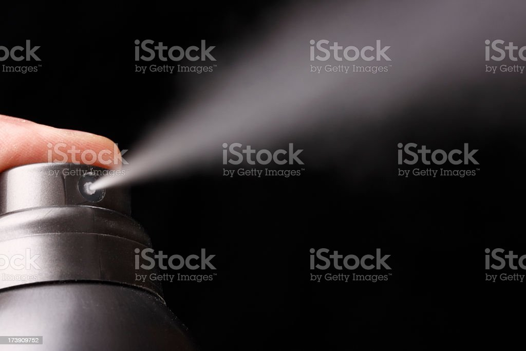 A person spraying an aerosol into a black background stock photo
