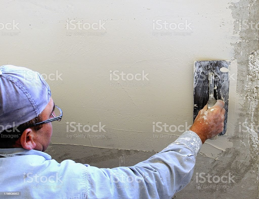 Person spreading mortar at construction site royalty-free stock photo