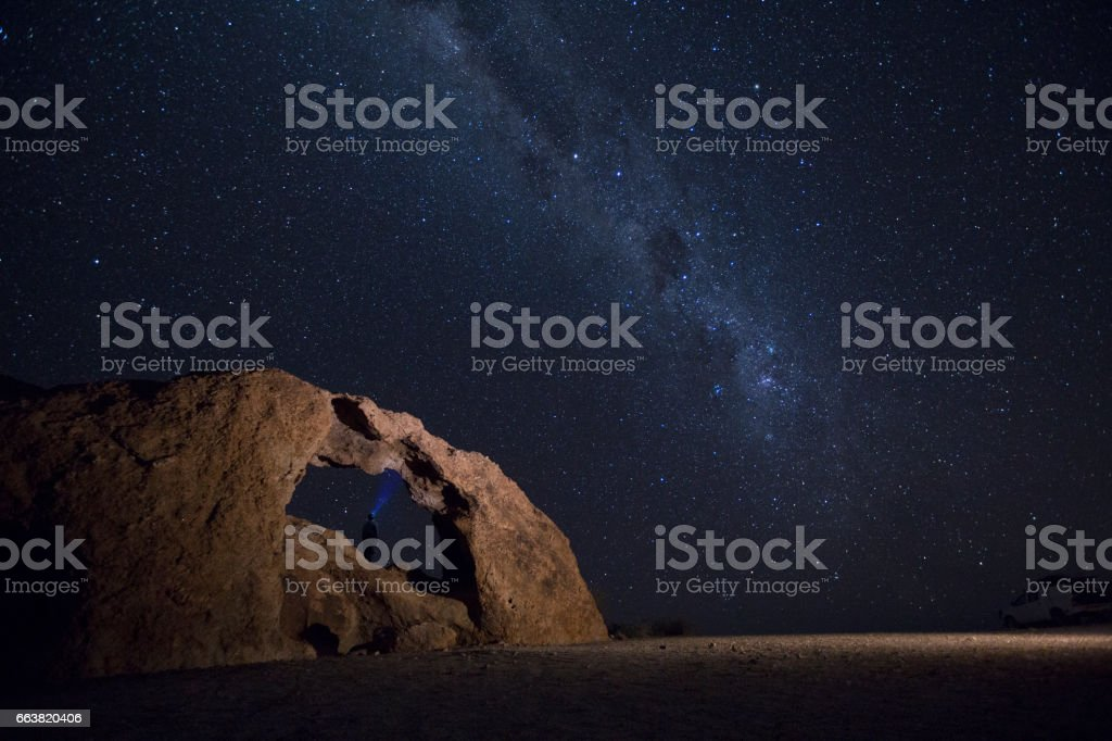 Person standing in a rock arch at night stock photo
