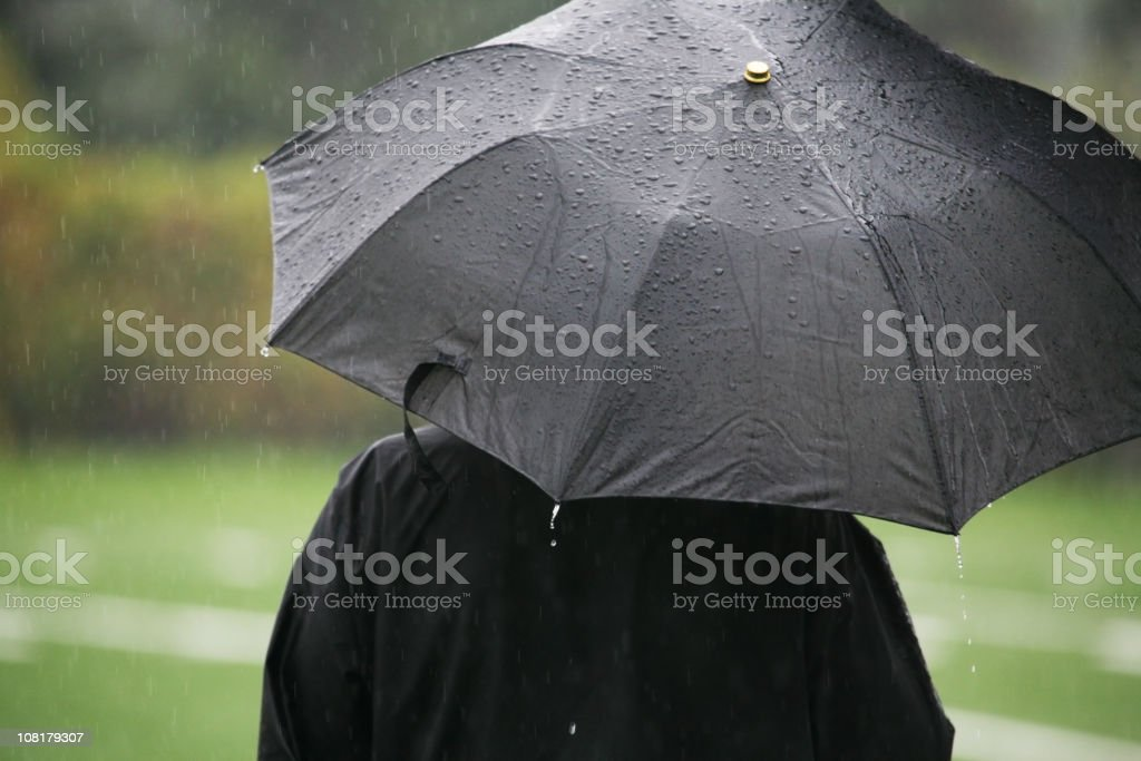 Person Standing in Rain with Black Umbrella royalty-free stock photo