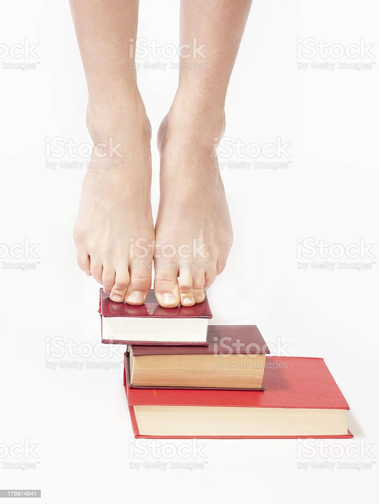 Person standing on a stack of books royalty-free stock photo