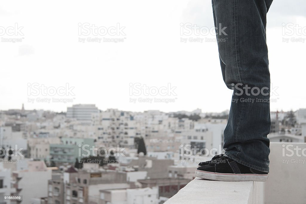 Person standing on the edge of tall building stock photo