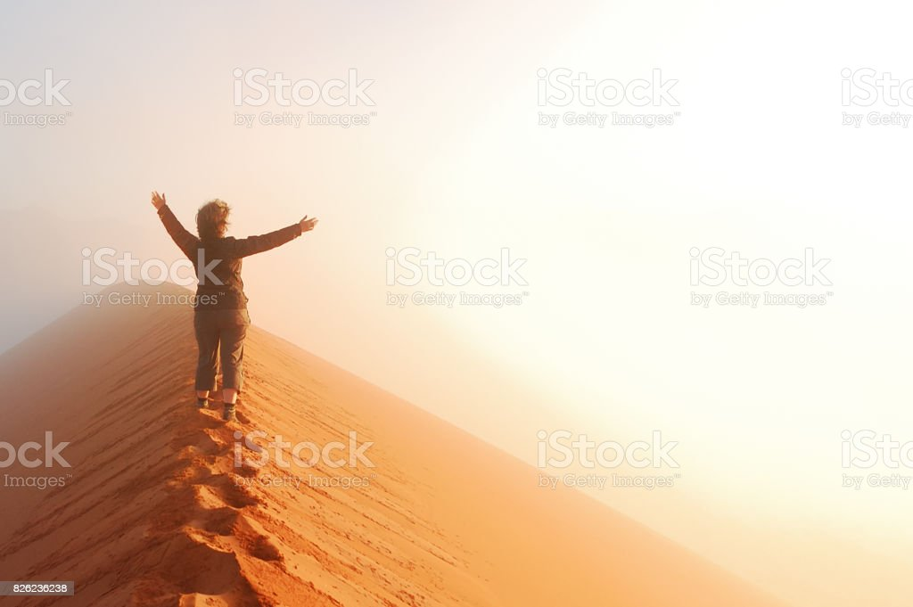 Person standing on top of dune in desert and looking at rising sun in mist with hands up, travel in Africa, Namibia stock photo
