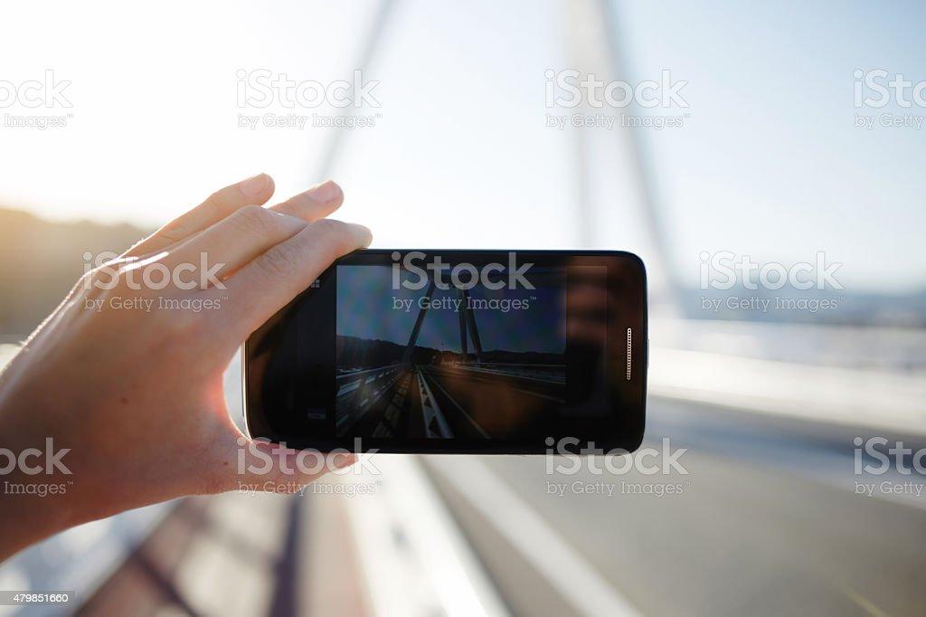 Person taking a photo of beautiful sunset using phone camera stock photo
