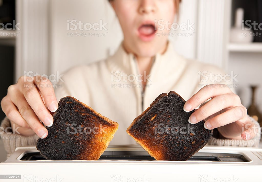 A person taking burnt toast out of the toaster stock photo