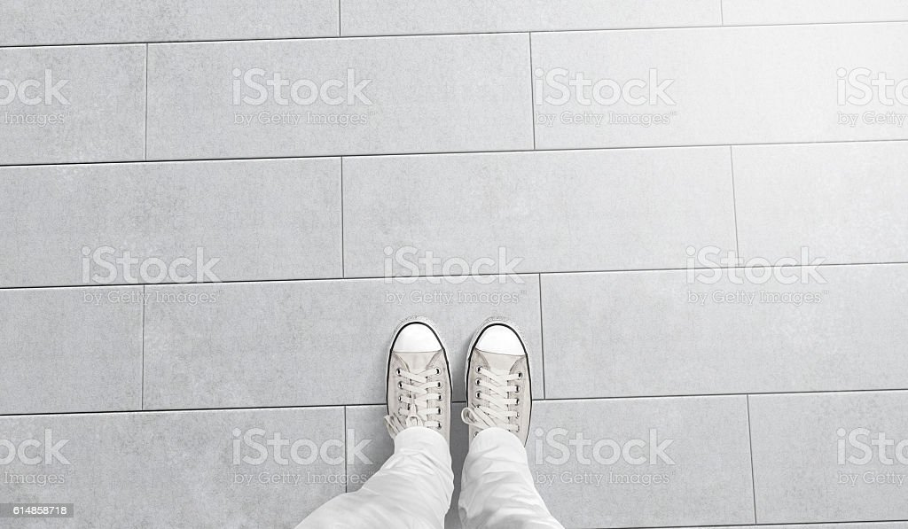 Person taking photo of his foots stand on blank floor stock photo