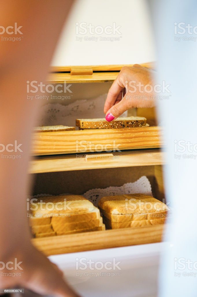 Person taking slice of bread stock photo