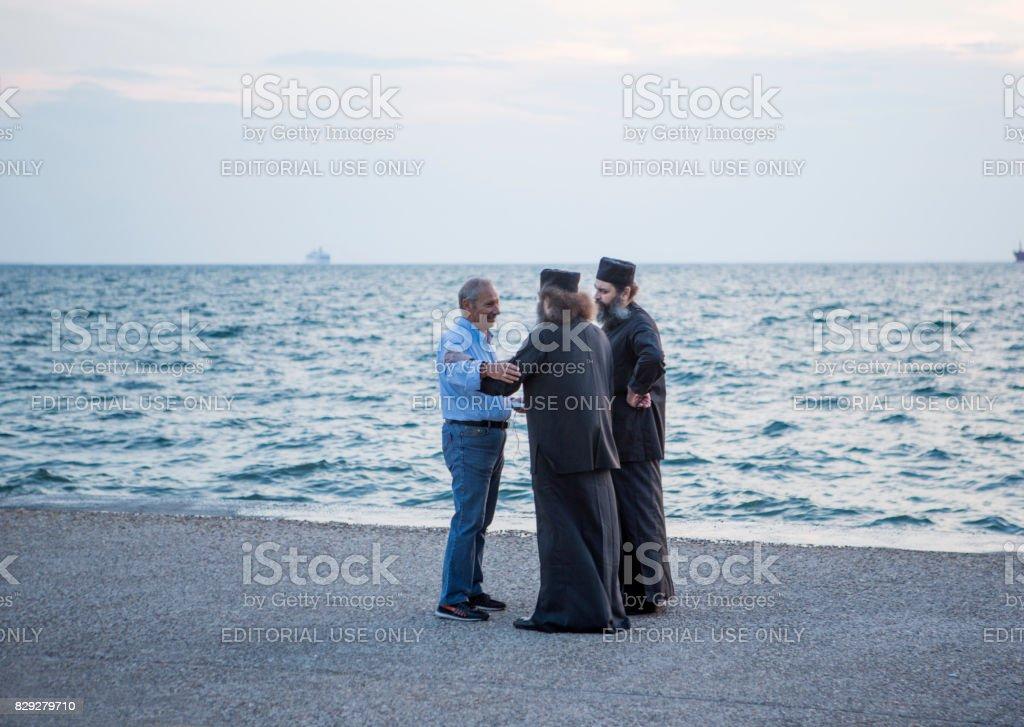 person talking to religious people at coast of Thessaloniki greece stock photo