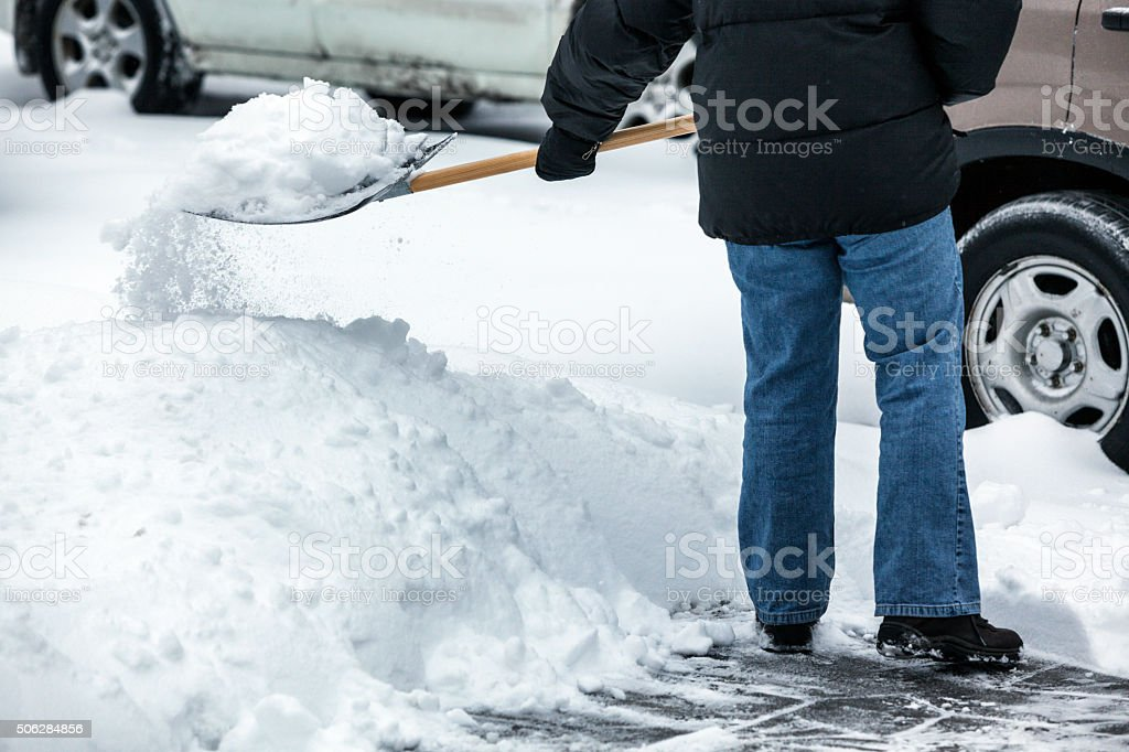 Person Throwing Snow from Footpath With Snow Shovel stock photo