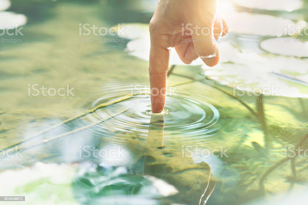 person touches the water with his hand stock photo