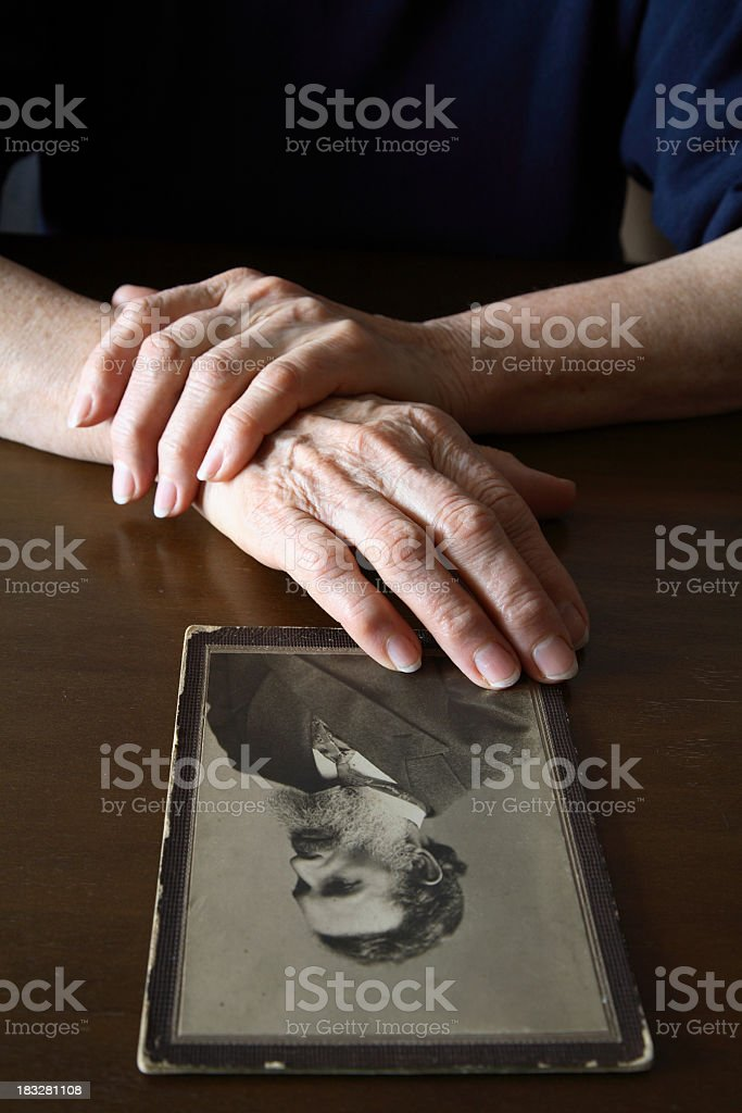 A person touching and viewing an old man portrait on a table royalty-free stock photo