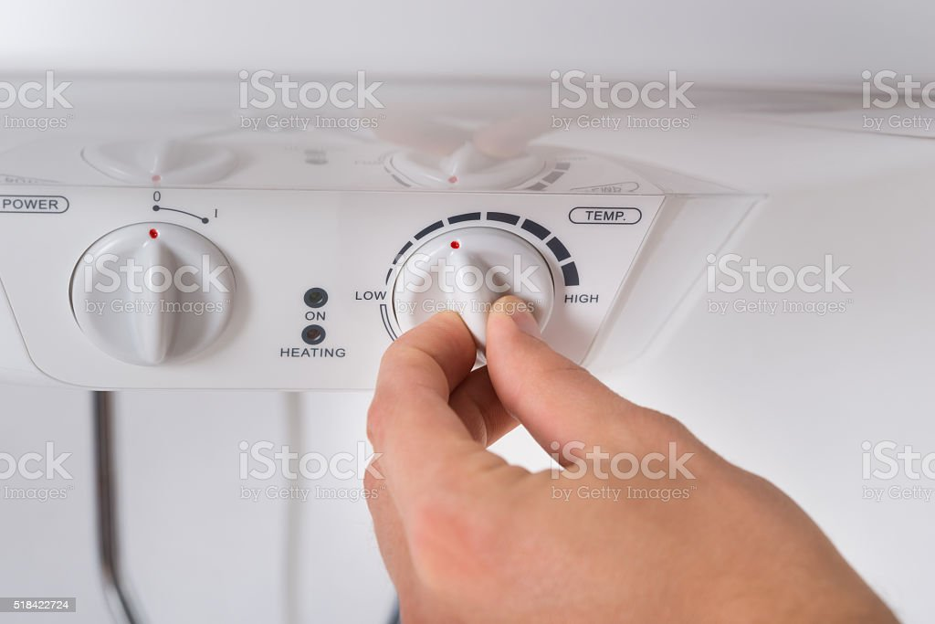 Person Turning The Knob Of Electric Boiler stock photo