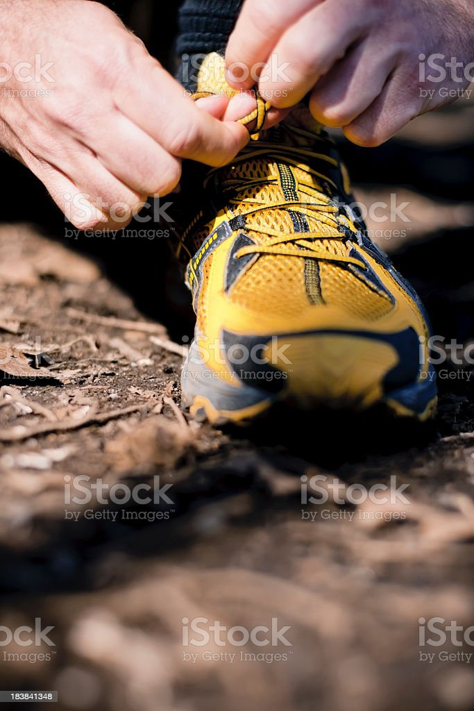 A person tying their yellow hiking shoes royalty-free stock photo