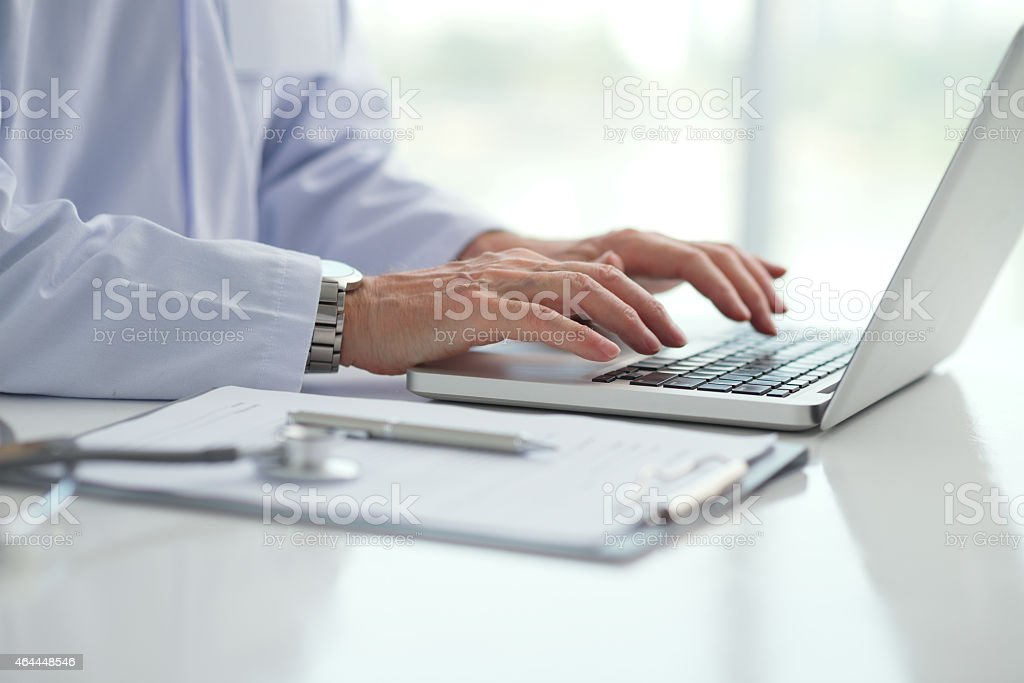 Person typing on computer on modern medical white desk stock photo