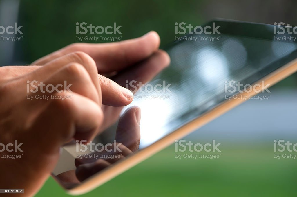Person using a digital tablet with reflections royalty-free stock photo