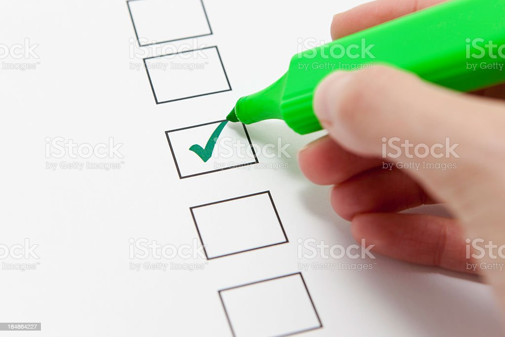 Person using a green highlighter to tick a form stock photo