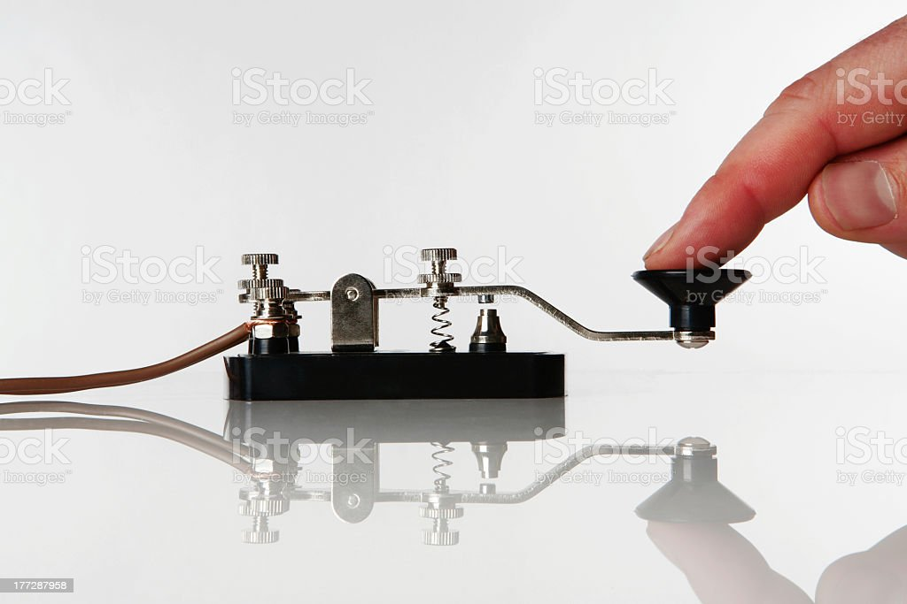 Person using a morse code machine on a white table stock photo