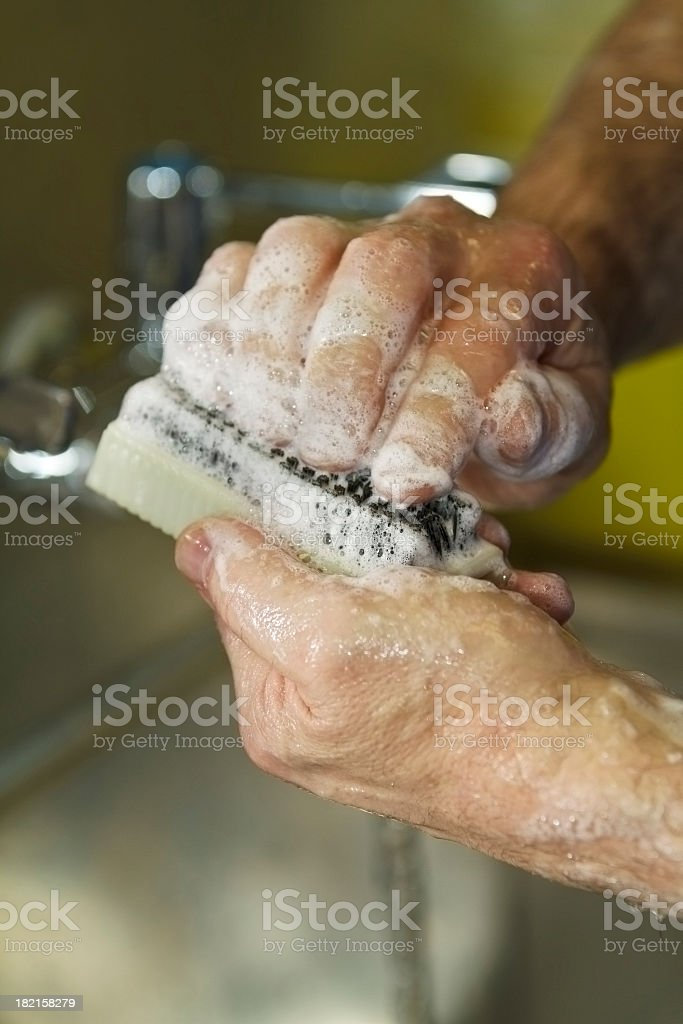 Person using a nail brush to wash hands stock photo