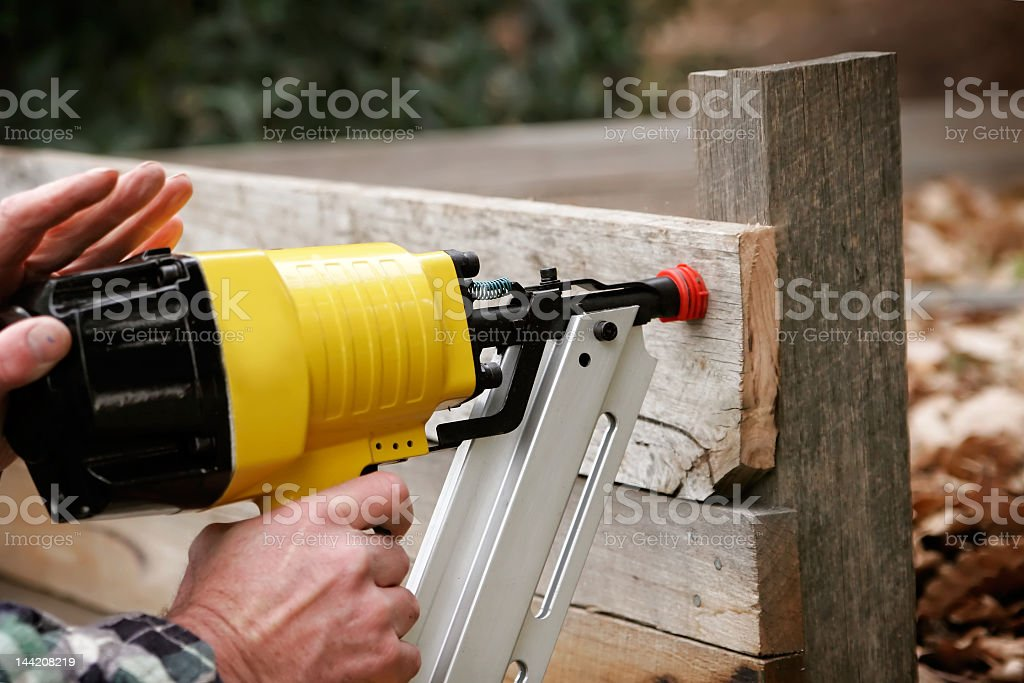 A person using a nail gun to put together wood stock photo