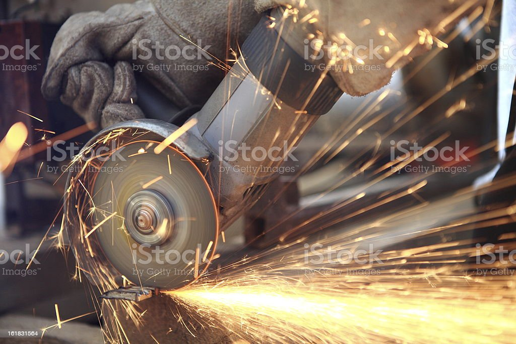 A person using a saw to cut metal royalty-free stock photo