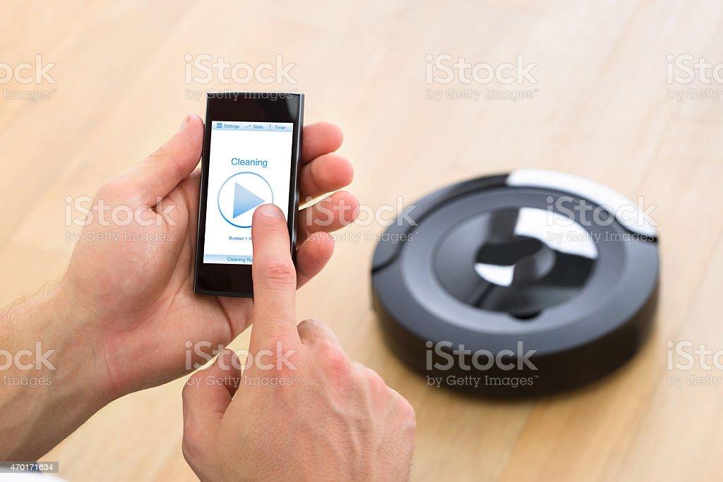Person Using Remote Control Of Robotic Vacuum Cleaner stock photo
