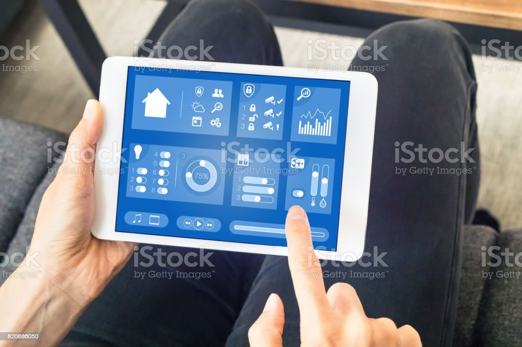 Person using smart home automation dashboard on digital tablet computer stock photo