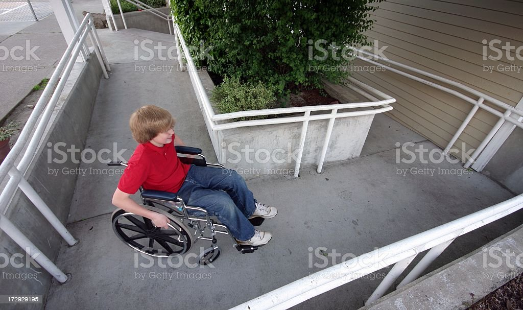 Person using wheelchair access ramp in an office building stock photo