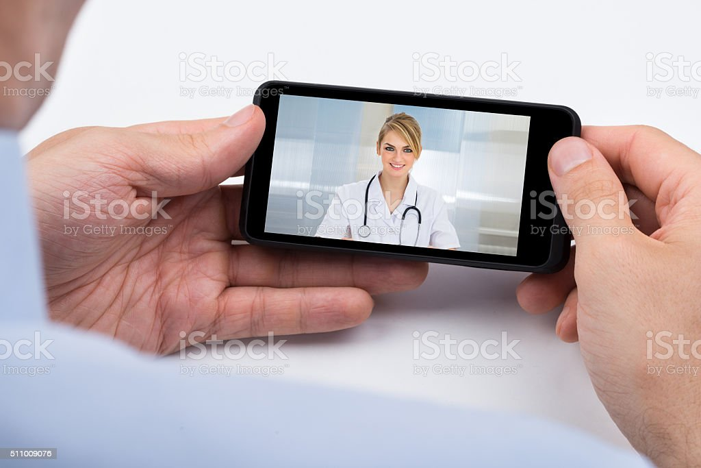 Person Videochatting With Doctor On Mobile Phone stock photo