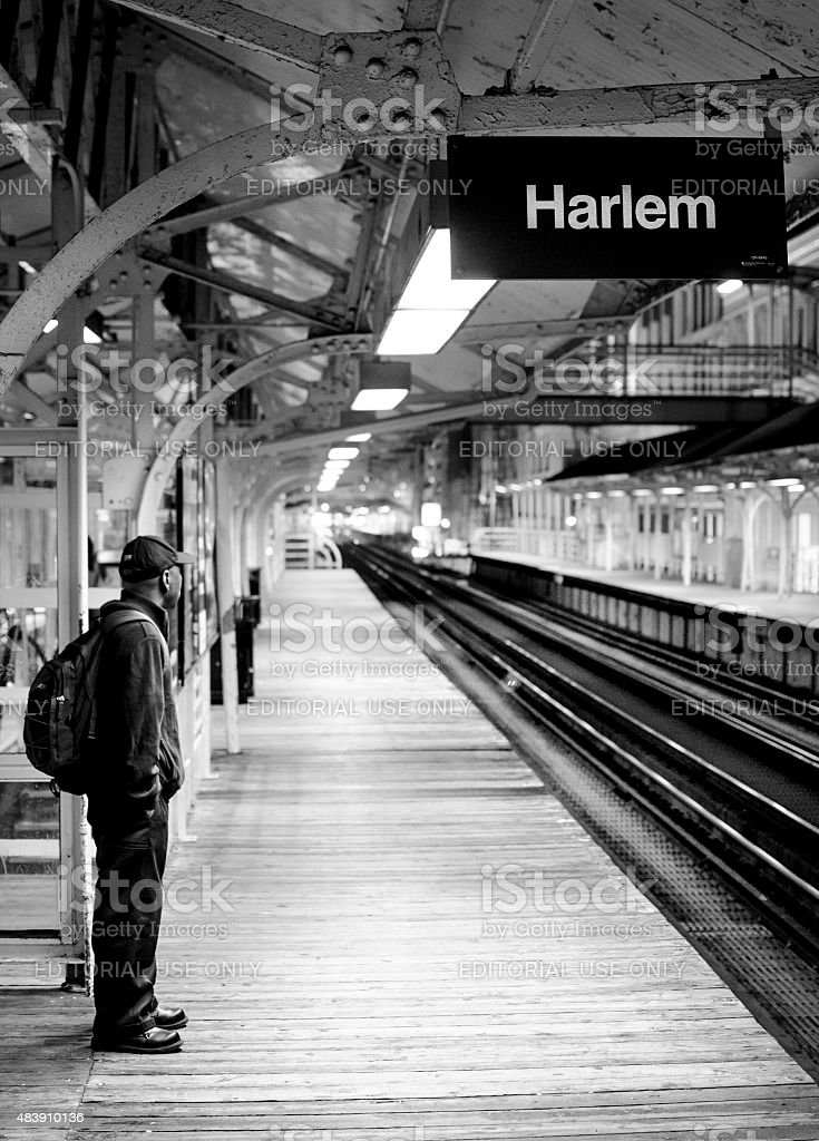 Person waiting for subway alone by traintracks stock photo