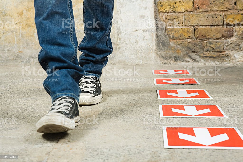 Person walking by arrows stock photo