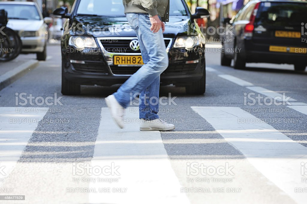 Person walking on zebra crossing in front of car stock photo