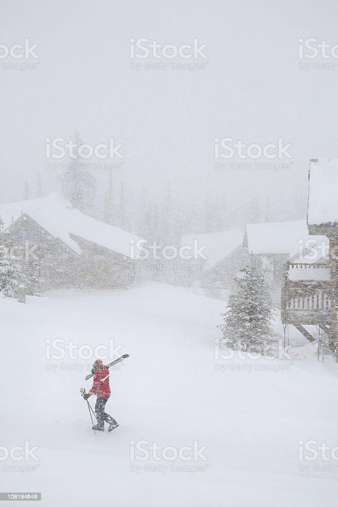 Person Walking Through Snow with Skis Near Lodge royalty-free stock photo