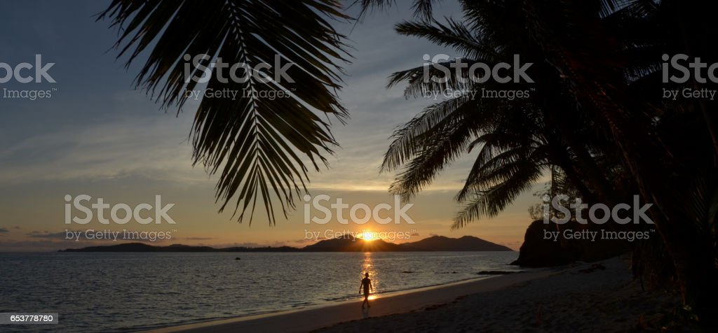 Person walks on the beach during tropical sunset stock photo