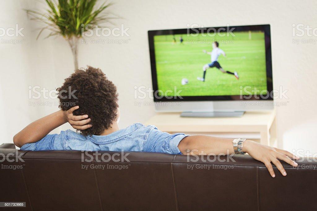 Person Watching Television Broadcasting Soccer Sport, Relaxing on Home Sofa stock photo