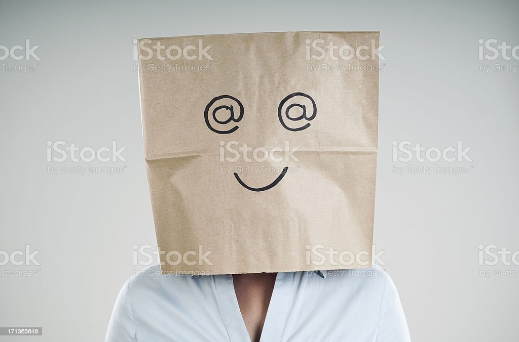 Person wearing a paper bag with @ symbol eyes and a smile stock photo