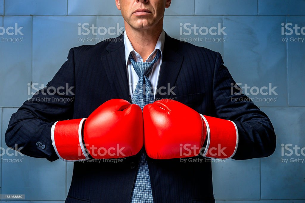 person wearing business suit and boxing gloves stock photo