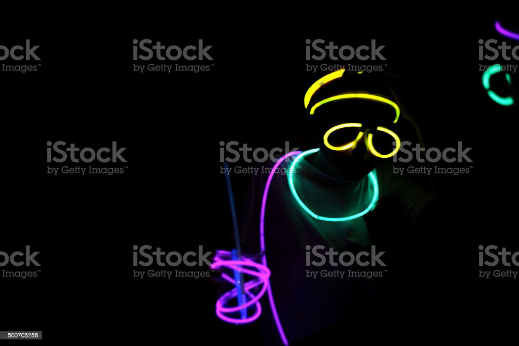 Person wearing colorful neon glow sticks at night stock photo