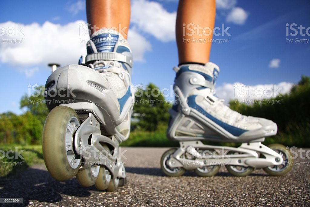 Person wearing gray and blue rollerblades on gravel stock photo