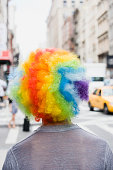 Person wearing rainbow clown wig in downtown city