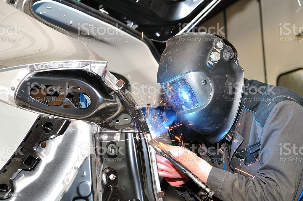 Person wearing welding mask welding part of car body stock photo