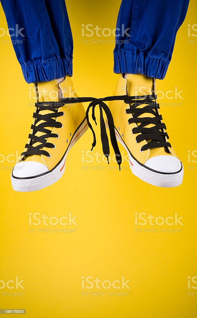 Person Wearing Yellow Shoes with Laces Tied Together royalty-free stock photo