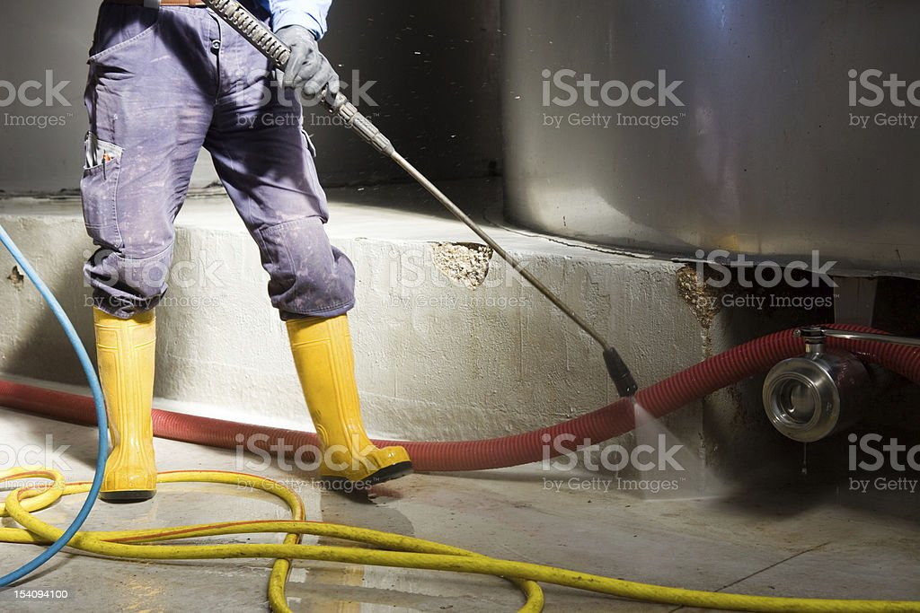 Person wearing yellow wellingtons jet spraying the floor royalty-free stock photo