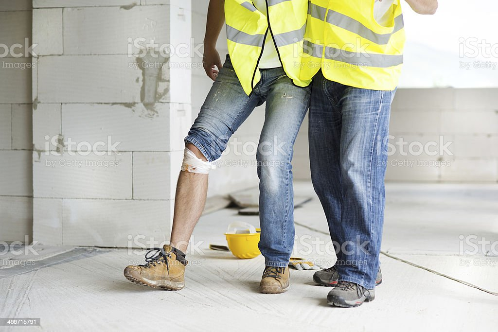 A person with a bandage on his knee is helped by another stock photo