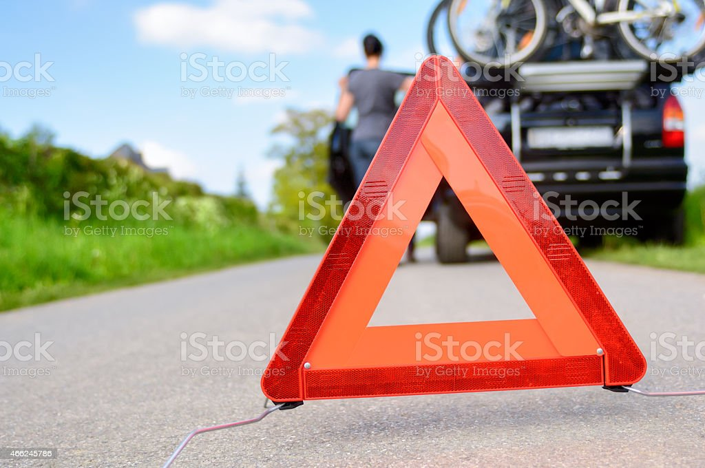 A person with a caution sign do to car trouble stock photo