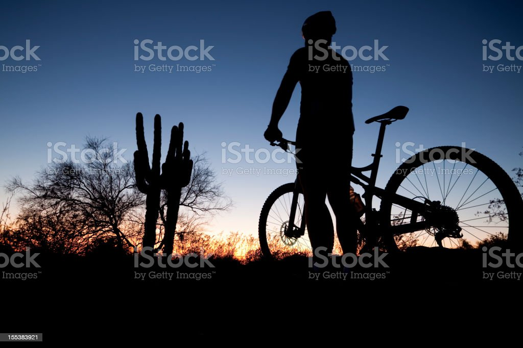 A person with a mountain bike stood at sunset stock photo